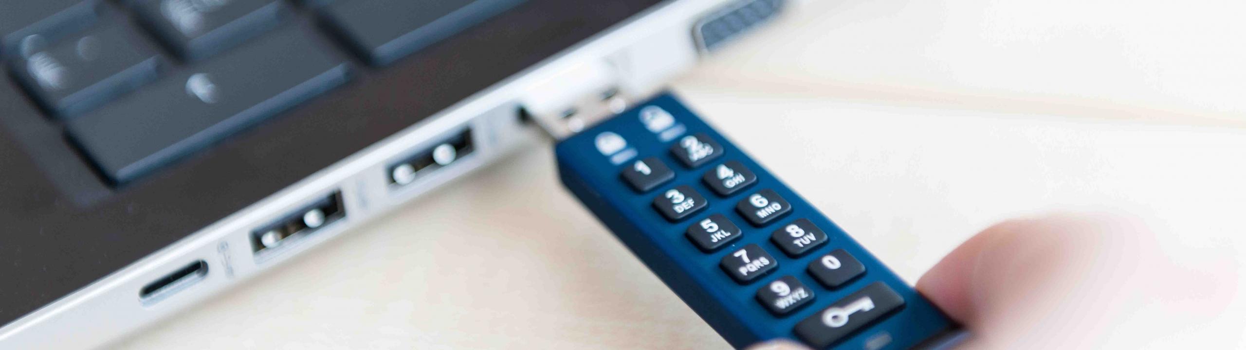 Verschlüsselter Stick wird in Laptop gesteckt.